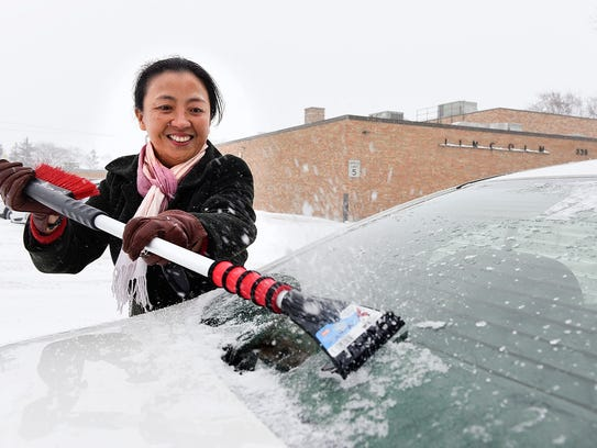 Sally Xiaoquing Du scrapes the ice off the back window