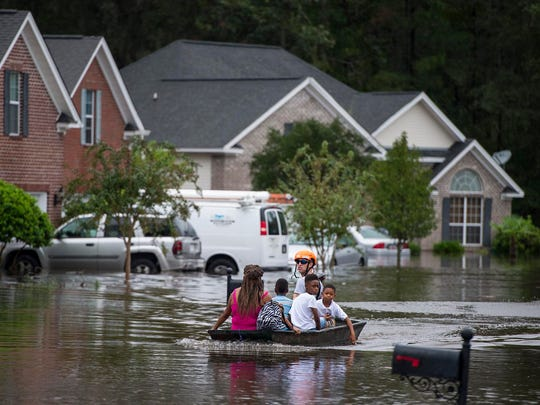 A member of the Pooler Fire Department uses a boat to move residents of homes on Tappan Zee Drive after Hurricane Matthew caused flooding in Pooler, Ga., a suburb of Savannah, Saturday, Oct. 8, 2016. (Josh Galemore/Savannah Morning News via AP)
