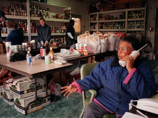 A file photo taken in 1998 of Evelyn Mount as she talks on the phone to potential donors. In the background, volunteers are seen getting food ready to go to needy families.