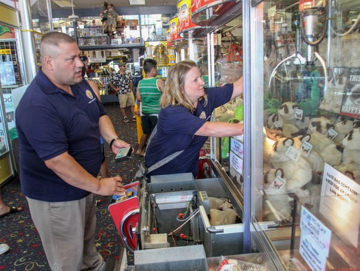 Point Pleasant Beach,  NJ       Joseph Chessere and Christine Donahue, investigators with the NJ Division of Consumer Affairs, inspect a crane game at Jenkinson's South Arcade on the Pt Pleasant Beach boardwalk.  070114  Tom Spader/Asbury Park Press