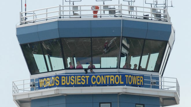 "A ""World's Busiest Control Tower"" banner hangs from the air traffic control tower at Wittman Regional Airport during EAA AirVenture 2012."