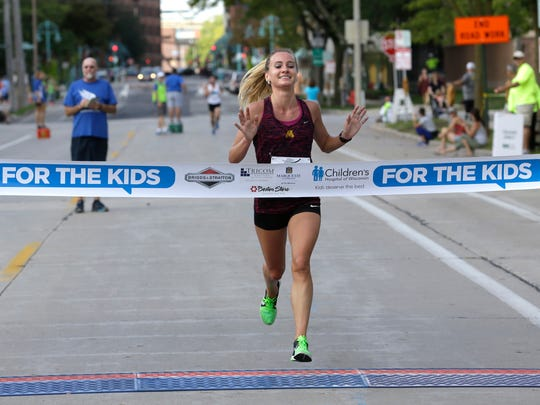 Liz Berkholtz finishes first in the women's division at the finish line to Briggs & Al's Run & Walk for Children's Hospital of Wisconsin near the Summeriest grounds on Saturday. In 38 years the event has raised more than $18 million. In 2015 there were 15,400 participants.