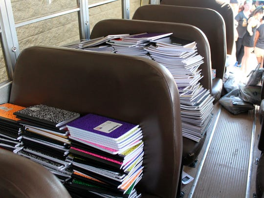 "Notebooks are seen stacked up in a school bus during the ""Stuff the Bus"" event. The bus was halfway filled with school supplies donated by locals for children in need."