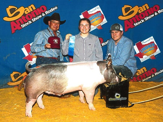 Alex Diaz, of Wylie High School, won first place in the Cross Division at the 2017 San Antonio Stock Show with her pig, Burrito. She is accompanied by her grandfather, Raymond Diaz, and Wylie High School ag teacher Reagan Richter.