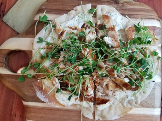 Banyan 320 Kitchen and Bar's flatbread topped with whipped herb goat cheese, caramelized onion, and chicken garnished with fresh pea shoots.