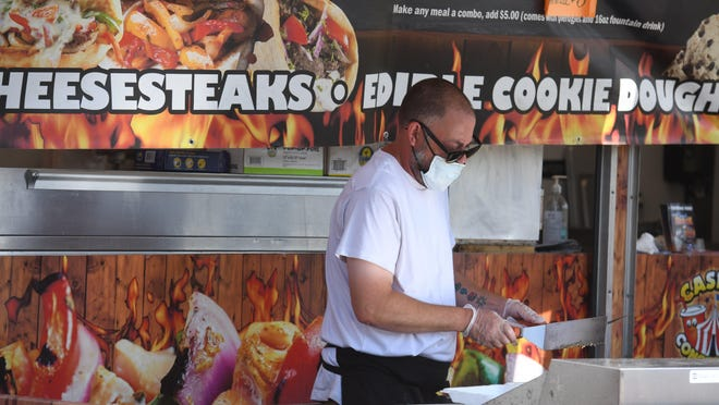 Bryan Szollosi, manager of North Canton-based Casey's Concession, grills some beef and veggies Tuesday to make a cheesesteak sandwich at the company's temporary setup spot on Lincoln Way E at 11th Street NE in Massillon. Szollosi said the business had 33 summer events planned in 2020, but due to the coronavirus, the number has shrunk to three.