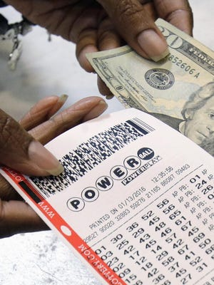 A clerk hands over a Powerball ticket for cash Jan. 13, 2016, at Tower City Lottery Stop in Cleveland.