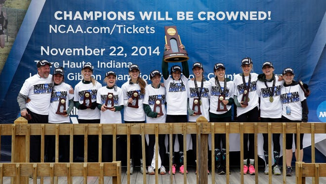 Members of the women's Michigan State cross country team hold the championship trophy after winning the women's NCAA Division I Cross-Country Championships on Saturday