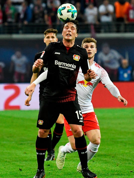 FILE - In this April 9, 2018 file photo Leverkusen's Julian Baumgartlinger, front, challenges for the ball against Leipzig's Timo Werner, right, during the German first division Bundesliga soccer match between RB Leipzig and Bayer Leverkusen in Leipzig, Germany.  Bayer Leverkusen is on course for a return to the Champions League with a host of young players promising further improvement under coach Heiko Herrlich. (AP Photo/Jens Meyer,file)