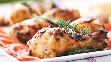 Roast chicken legs, decorated with slices of tomato on a white plate, perfect food for  a warm summer evening.
