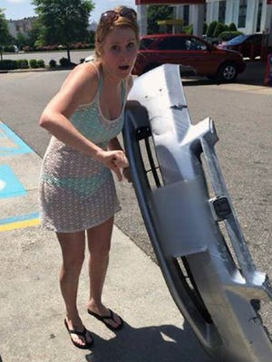 Allyson Conroy poses with the bumper a driver left behind May 25, 2015, after hitting her friend's SUV in Chesapeake, Va.