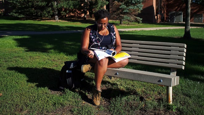 """Augustana University student Sara Pelahun Birhe, who works three jobs as well as being a full-time student, works on homework for a government class Tuesday, Sept. 27, 2016, on the Augie campus in Sioux Falls. """"Right now is homework/friend time, and all my friends are doing homework,"""" she said while finding a spot to study outside."""