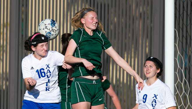 Xavier College Prep's Kendall Ward (16) and Flagstaff's Kristen Davison head the ball during their girls soccer game in Phoenix on Friday, January 9, 2015.