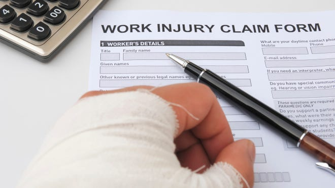 Person filling out work injury claim form with bandaged hand.