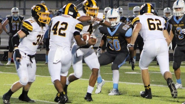 Keyser's Drae Allen (42) hands the ball off to Zion Powell (4) on the inside reverse as quarterback Gavin Root (31) looks on. Tribune photo by Chapin Jewell
