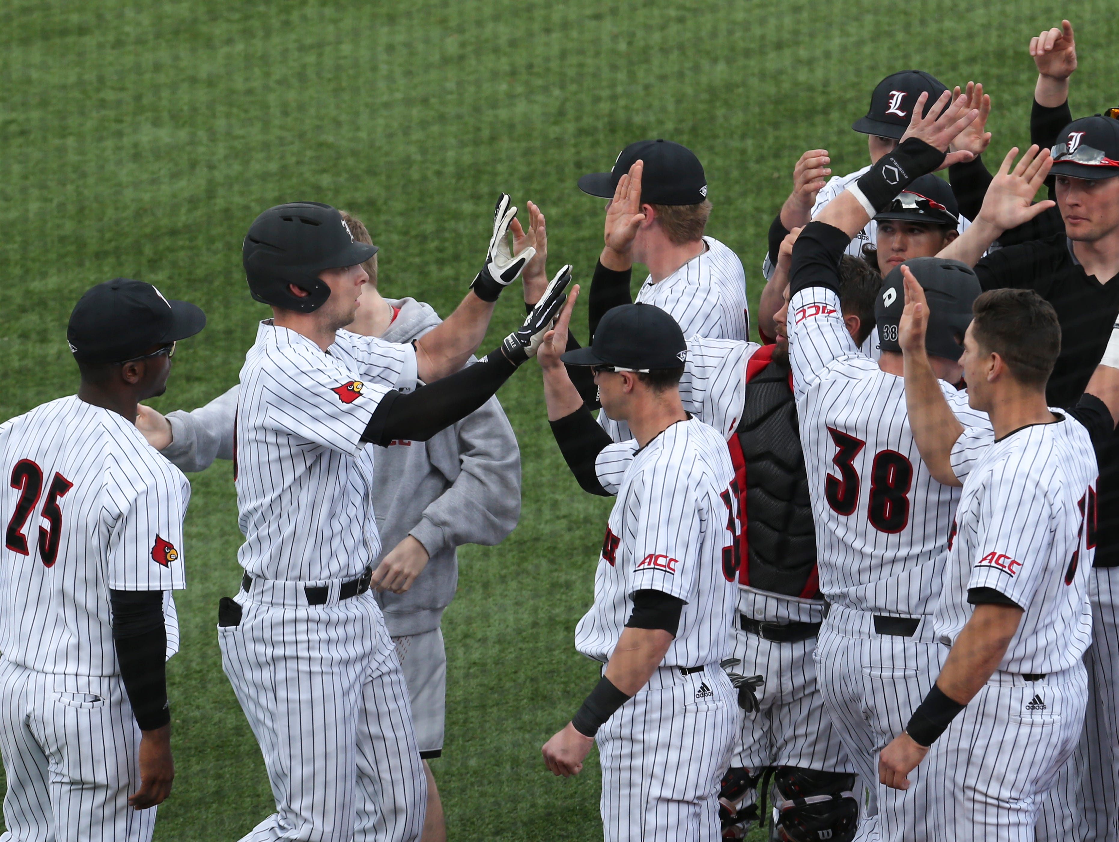 U of L's Drew Ellis (10), left, was greeted by teammates after hitting a home run against Eastern Kentucky at Jim Patterson Stadium. Feb. 22, 2017