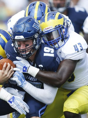 Delaware linebackers Larry Spears (43) and Charles Bell (5) swarm Villanova quarterback John Robertson in the third quarter of the Blue Hens' 28-21 loss Sept. 19.