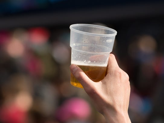 A man holds up plastic glass containing beer at outdoor