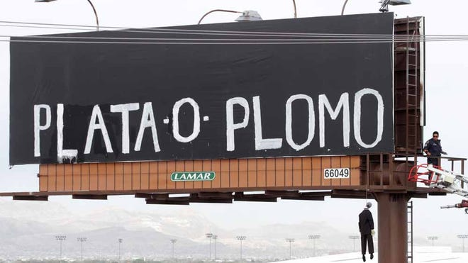 """An El Paso police officer checks a makeshift mannequin that was left hanging on a billboard along with a message that translates to """"silver or lead."""""""