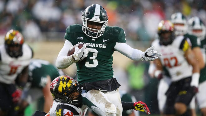 LJ Scott #3 of the Michigan State Spartans tries to run through the tackle of Antoine Brooks Jr. #25 of the Maryland Terrapins during the first half of the game against Maryland on Saturday, Nov. 18, 2017, at Spartan Stadium.