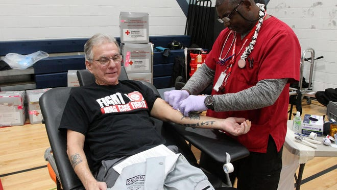 Roy Leavenworth gives a donation at the Battle of the Badges blood drive at West New Bern Recreation Center. The American Red Cross - Battle of the Badges blood drive event encourages a friendly competition for donations with the City of New Bern, City of New Bern Fire-Rescue and the New Bern Police Department.