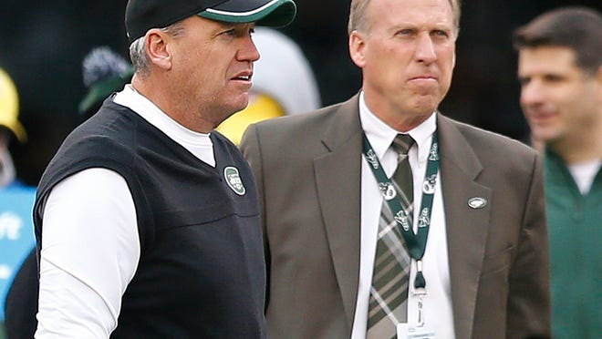 New York Jets head coach Rex Ryan, left, and general manager John Idzik watch their team warm up before an NFL football game against the New England Patriots, in East Rutherford, N.J. Jets owner Woody Johnson fired Ryan and Idzik on Monday after one of the most disappointing seasons in franchise history.