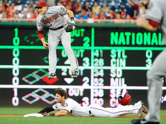 Aug. 4, 2015; Washington, D.C.; Washington Nationals right fielder Bryce Harper (34) slides into second under the leaping Arizona Diamondbacks shortstop Nick Ahmed (13) for a double during the first inning at Nationals Park.