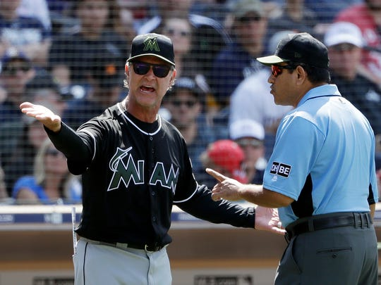 Miami Marlins manager Don Mattingly, left, has a word with third base umpire Alfonso Marquez during the seventh inning of a baseball game against the San Diego Padre, Monday, May 28, 2018, in San Diego. (AP Photo/Gregory Bull)
