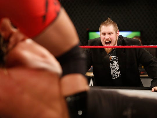 Manager Josh Ashcraft cheers on his wrestler during