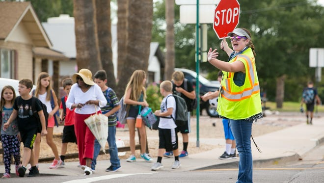 Crossing guard Samantha Maskey helps parents and students cross the street outside Pima Elementary School in Scottsdale on Tuesday, August 25, 2015.
