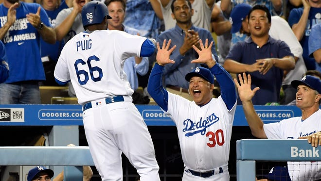 Puig celebrates a home run against the Giants with manager Dave Roberts.