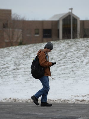 A student checks his phone while walking on campus Wednesday, Jan. 13, 2016, at Indiana University East in Richmond.