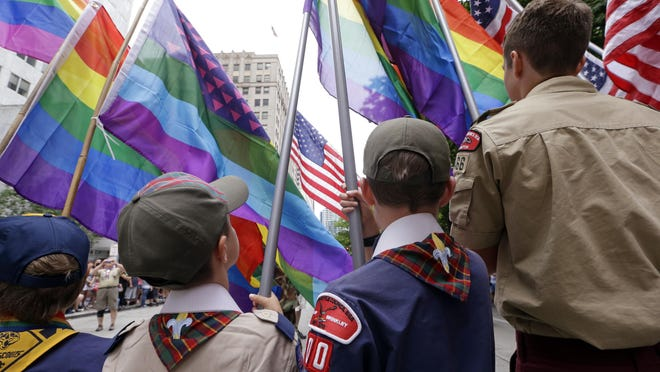 In this Sunday, June 28 file photo, Cub Scouts and Boy Scouts prepare to lead marchers while waving rainbow-colored flags at the 41st annual Pride Parade in Seattle, two days after the U.S. Supreme Court legalized gay marriage nationwide. On Monday, July 27, the Texas-based Boy Scouts of America ended its blanket ban on gay adult leaders but will allow church-sponsored Scout units to maintain the exclusion for religious reasons.