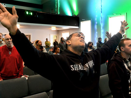 James Johnson of Sewickley gives thanks during a worship service Sunday at the Allegheny Center Alliance Church in Pittsburgh, Pa.