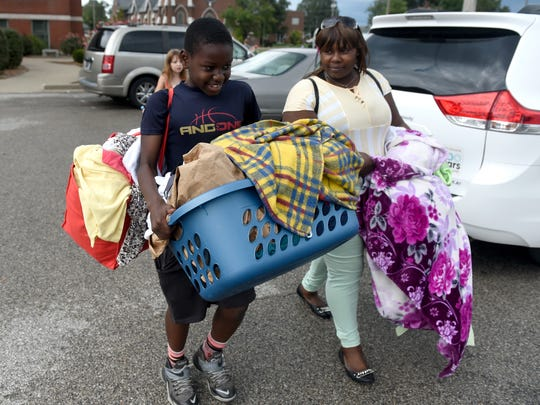 Angelo St. Louis, 11, helps his mother Marianie Sanon carry laundry outside of their apartment in Evansville recently.   Sanon was one of 21 Haitian passengers injured when the van they were being transported in wrecked on Interstate 69 while traveling to their worksite on Sept., 24, 2015.  Two passengers died and several others, including Sanon, were severely injured.