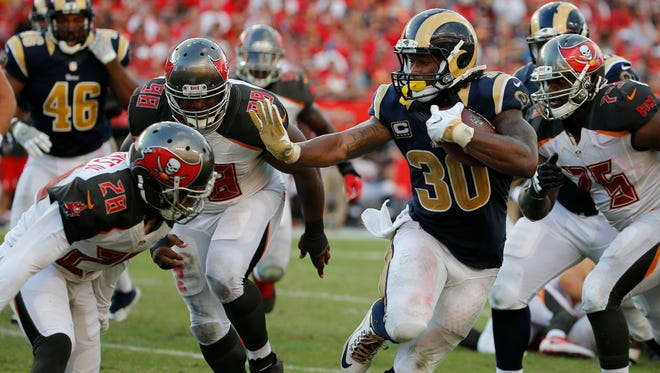 Sep 25, 2016: Los Angeles Rams running back Todd Gurley (30) stiff arms Tampa Bay Buccaneers cornerback Vernon Hargreaves (28) during the second half at Raymond James Stadium.