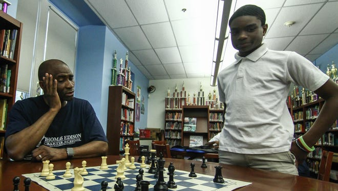Principal Salome Thomas-EL (left) discusses possible chess moves with Mark Coney, 13, during an after-school chess session last year at Thomas Edison Charter School in Wilmington.