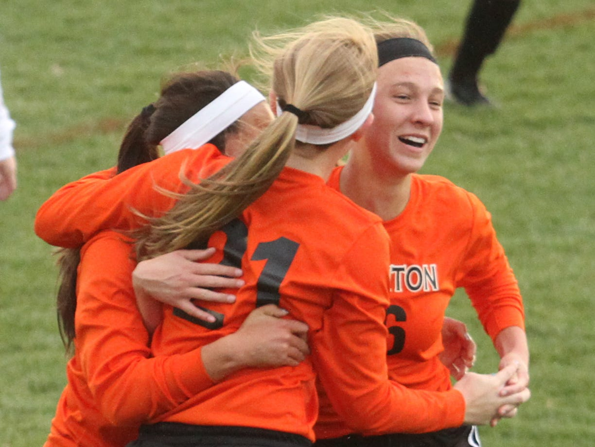 Mackenzie Chwalibog, center, is hugged by Brighton teammates after scoring a goal last month. The Bulldogs celebrated their first Lakes Conference championship in four years on Thursday night.