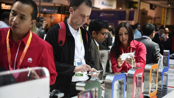 Attendees examine smartphones at the Consumer Electronics Show on Jan. 6.