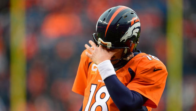 Denver Broncos quarterback Peyton Manning (18) after taking a hard hit during the first quarter against the Indianapolis Colts in the 2014 AFC Divisional playoff football game at Sports Authority Field at Mile High.
