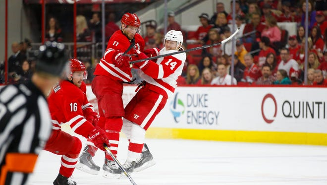 Carolina Hurricanes forward Jordan Staal (11) checks the Detroit Red Wings forward Gustav Nyquist (14) during the second period at PNC Arena.