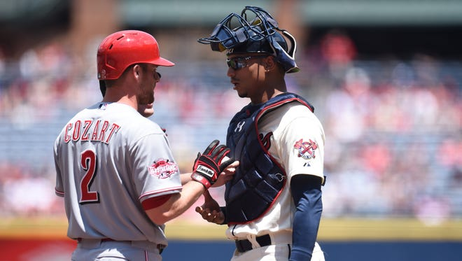 Reds shortstop Zack Cozart has words with Braves catcher Christian Bethancourt after being hit by a pitch during the first inning at Turner Field.