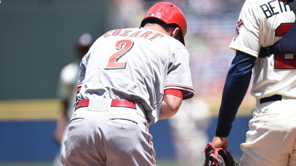 Reds shortstop Zack Cozart reacts after being hit by