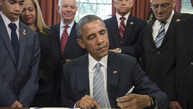 President Obama signs the Rafael Ramos and Wenjian Liu National Blue Alert Act of 2015 in the Oval Office of the White House Tuesday. The act, named after two police officers who were killed in New York, will assist the National Blue Alert system to apprehend violent criminals who have injured or killed police officers or who have made an imminent or credible threat to cause serious injury or death of a law enforcement officer.