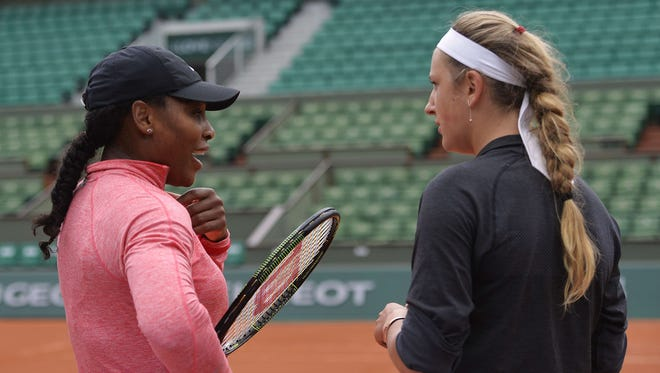Serena Williams speaks with Victoria Azarenka during a training session ahead of the French Open.