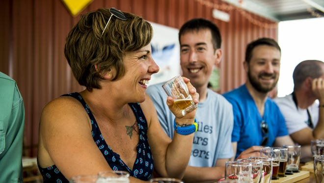 Megan Brummer sips a beer while conversing with friends during a tour of Bayou Teche Brewing.