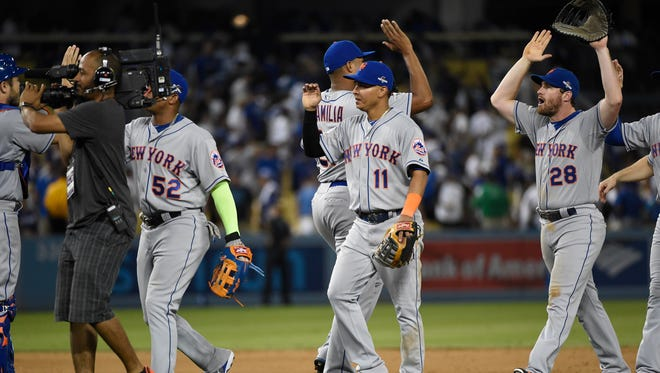 New York Mets shortstop Ruben Tejada (11) and second baseman Daniel Murphy (28) celebrate the 3-1 victory against the Los Angeles Dodgers in game one of the NLDS at Dodger Stadium.