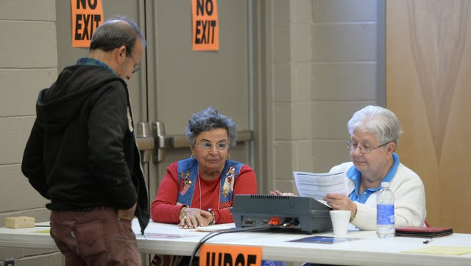 Poll workers assign an access code for a voting machine last week during early voting at First English Lutheran Church in Richmond.