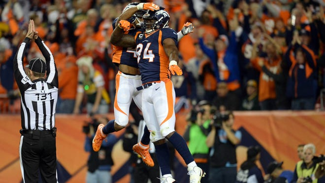 Denver Broncos outside linebacker DeMarcus Ware (94) celebrates his sack and safety of Green Bay Packers quarterback Aaron Rodgers (12) (not pictured) with strong safety T.J. Ward (43) in the fourth quarter at Sports Authority Field at Mile High.