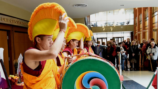 Tibetan Monks adjust their headdress prior to an opening ceremony Monday at The Sheid on the Arkansas State University Mountain Home campus. The monks will be working through Thursday to complete a Mandala, a painting created from colorful grains of sand.